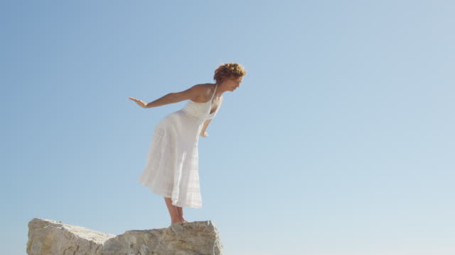 young woman practising yoga on rock against blue sky