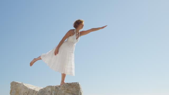 young woman practising yoga on rock against blue sky - auf einem bein stock-videos und b-roll-filmmaterial
