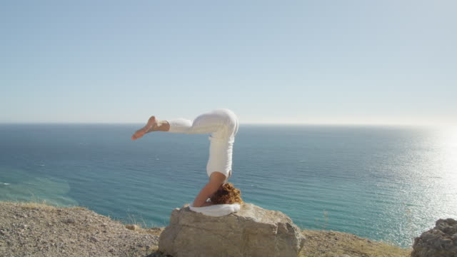 young woman practising yoga on rock against blue sky with ocean in background