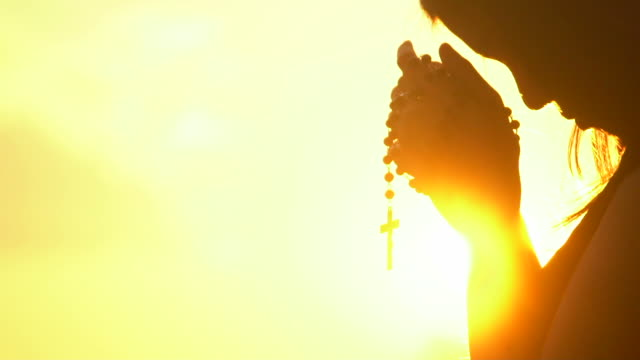 young woman praying with cross on beautiful sunset - catholicism stock videos & royalty-free footage