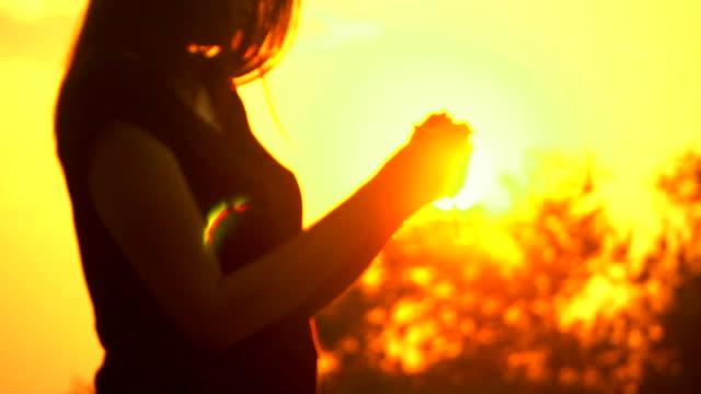 vídeos y material grabado en eventos de stock de joven orando con la cruz en la hermosa puesta de sol - baptista