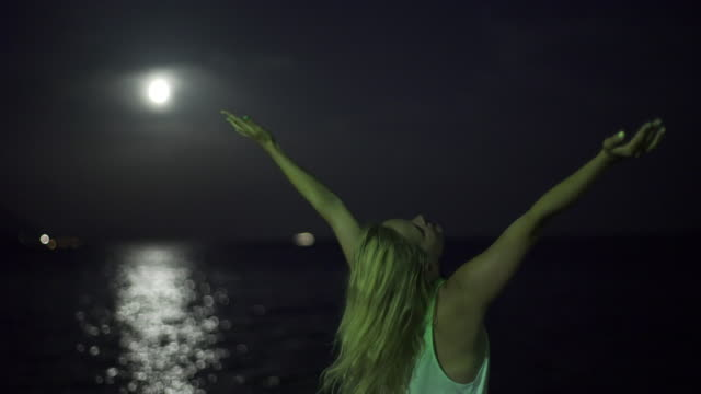Young woman praying with full moon.