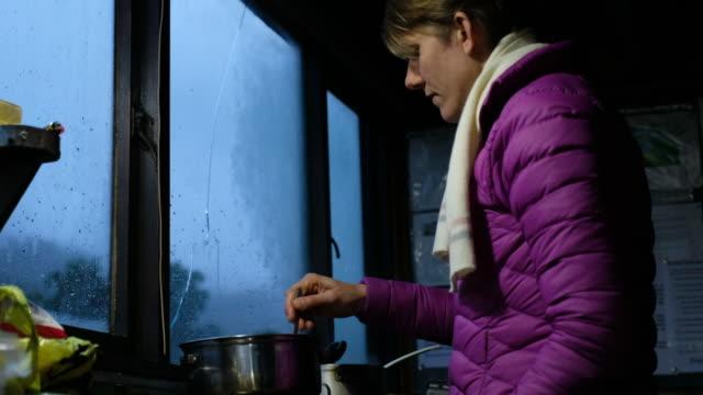 vídeos de stock e filmes b-roll de young woman prepares some warm food in the mountain hut - cabana estrutura construída