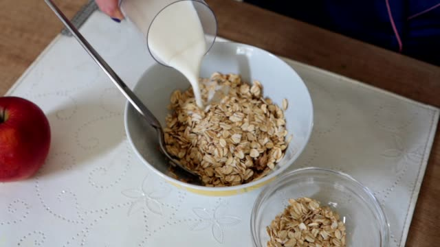 young woman preparing a healthy breakfast - breakfast cereal stock videos and b-roll footage