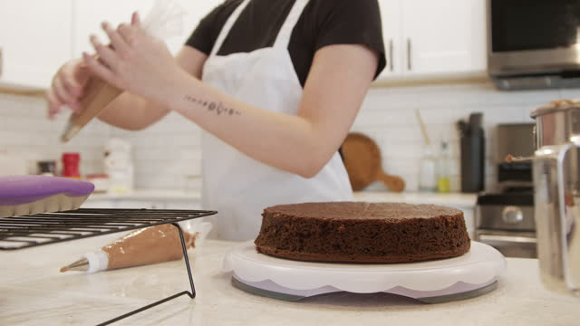 young woman preparing an icing bag with delicious chocolate buttercream frosting - decoration stock videos & royalty-free footage