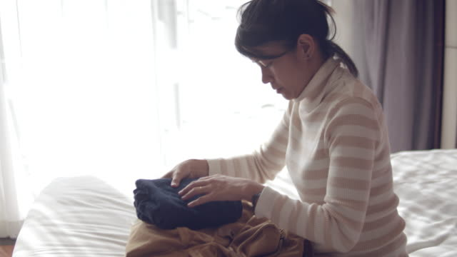 Young woman preparing bag for travel at home.