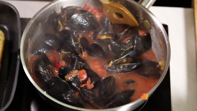young woman preparing blue mussels dish with white wine,chili pepper and parsley at home - french food stock videos & royalty-free footage