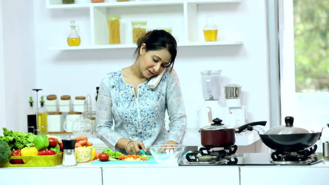 ms young woman preparing food and talking with phone in kitchen - cordless phone stock videos & royalty-free footage