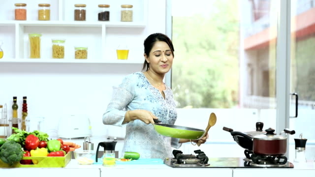 ms pan young woman preparing food in kitchen - kochgeschirr stock-videos und b-roll-filmmaterial
