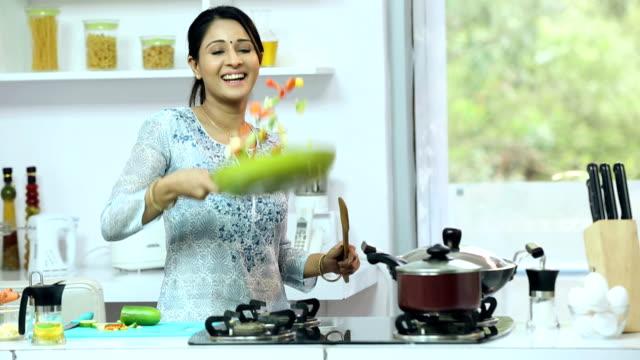ms young woman preparing food in kitchen - werfen stock-videos und b-roll-filmmaterial