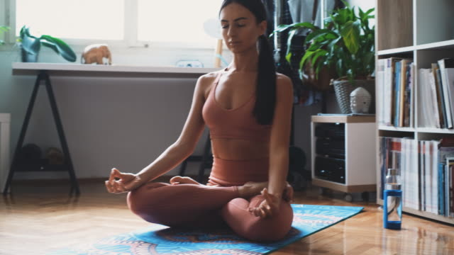 young woman preparing for meditation and sitting comfortably in the lotus position at home - mudra stock videos & royalty-free footage