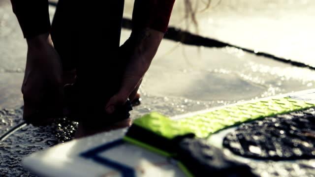 vídeos de stock, filmes e b-roll de jovem mulher se preparando para o surf. anexar uma prancha de surf - diving suit