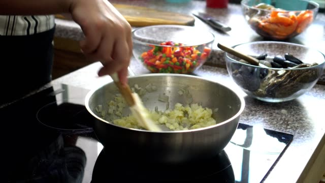 vídeos de stock e filmes b-roll de young woman preparing paella - cebola