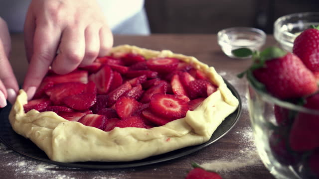 young woman preparing strawberry galette or open strawberry pie - french food stock videos & royalty-free footage