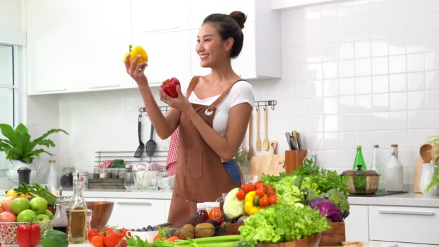 a young woman preparing vegetables for healthy meal and salad - kitchenware department stock videos and b-roll footage