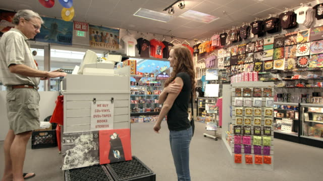 stockvideo's en b-roll-footage met ws pan young woman presents pack of dvds to record store cashier while other customers go through long racks of used dvds sold in the store / palm desert, california, usa - dvd