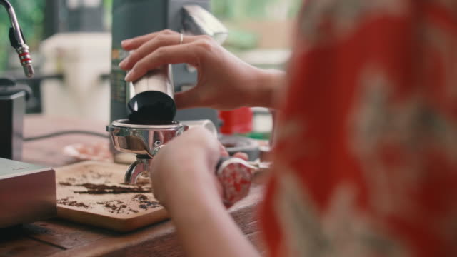 young woman presses ground coffee using hand. - kitchenware department stock videos and b-roll footage