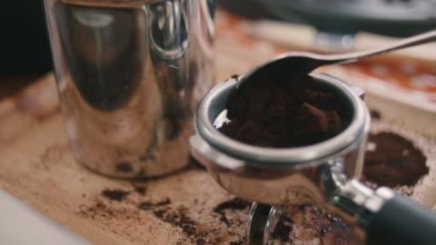 vidéos et rushes de jeune femme appuie sur du café moulu à l'aide de la main. - préparation
