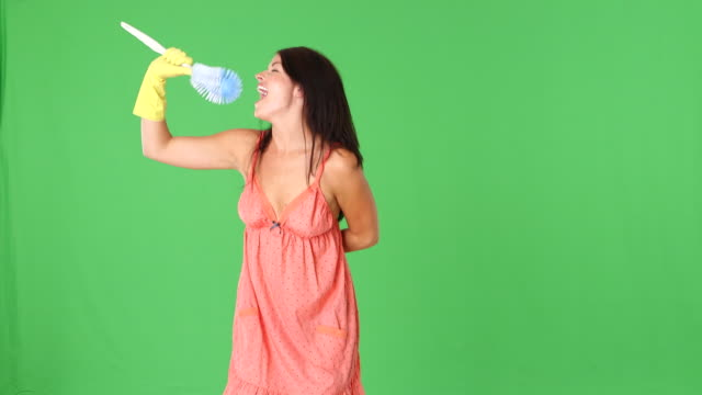 young woman pretending to be a singing star with toilet brush and sponge - cantare video stock e b–roll