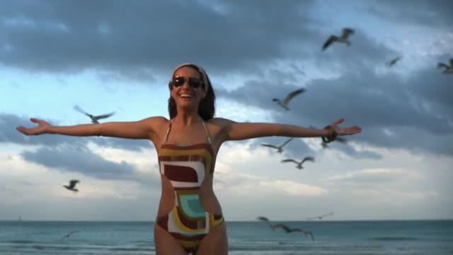 ms slo mo young woman pretending to fly on beach / south beach, florida, usa - kopf nach hinten stock-videos und b-roll-filmmaterial