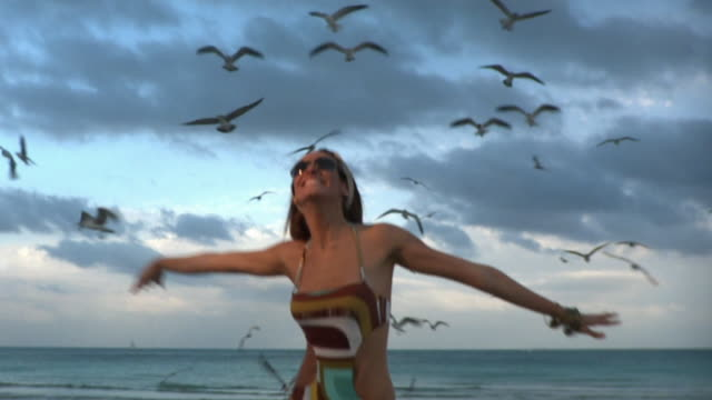 ms slo mo young woman pretending to fly on beach / south beach, florida, usa - swimming costume stock videos & royalty-free footage