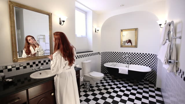A young woman primps in the bathroom mirror of the historic American Colony Hotel in Jerusalem.