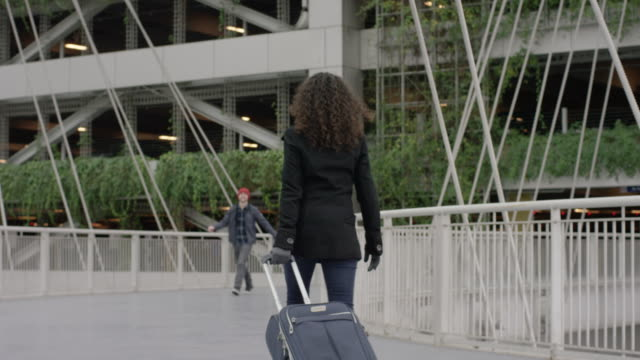 A Young Ethnic Woman Pulling Her Suitcase Re-Unites with Her Husband