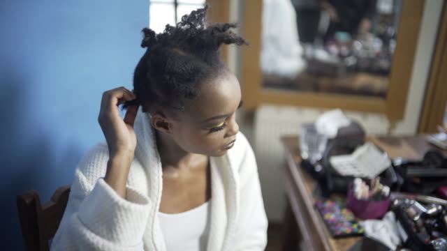 A young woman pulling out her afro hair braids.