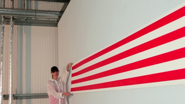 young woman pulling striped wallpaper along wall - 引く点の映像素材/bロール