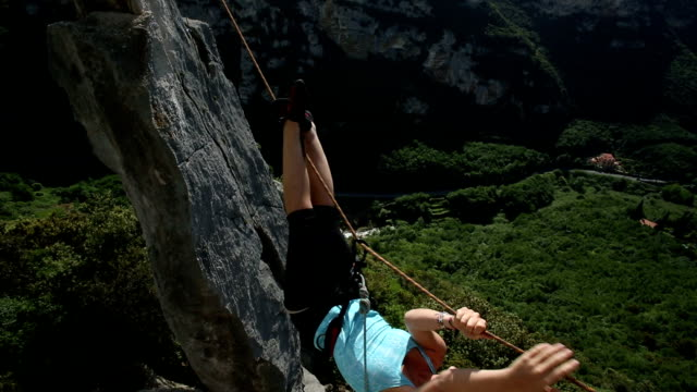 young woman pulls herself across tyrolean traverse - life belt stock videos & royalty-free footage