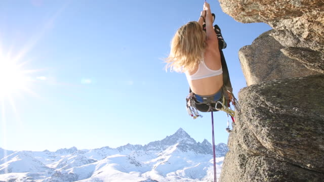 Young woman pulls herself up climbing rope, vertical cliff