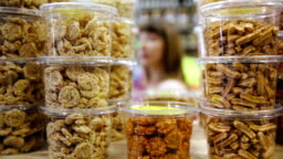 Young woman purchases dried fruits and nuts in grocery
