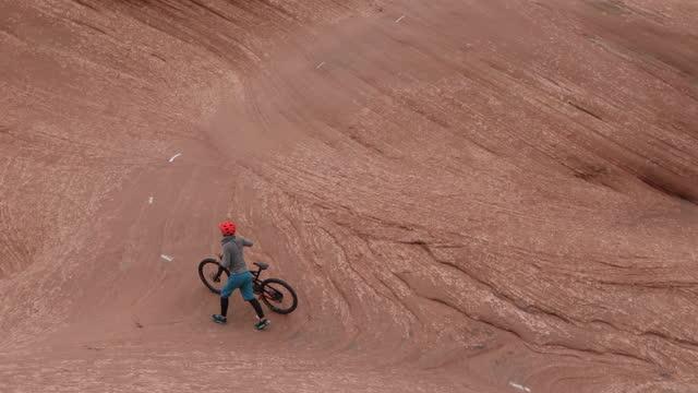 young woman pushes bike up slickrock rock slab - moab utah stock videos & royalty-free footage
