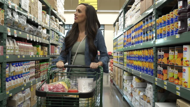 young woman pushing a shopping cart in a warehouse supermarket - canned food stock videos & royalty-free footage