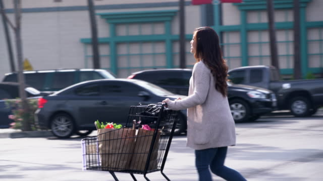 ms young woman pushing a shopping cart through a parking lot - parken stock-videos und b-roll-filmmaterial