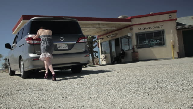 ms young woman pushing car to american gas station / palmdale, ca, united states  - schieben stock-videos und b-roll-filmmaterial