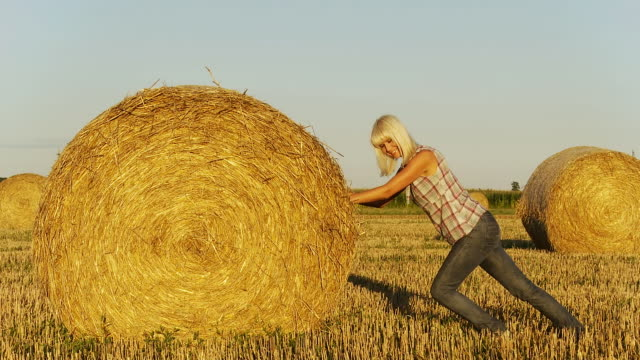 HD: Young Woman Pushing Hay Bale