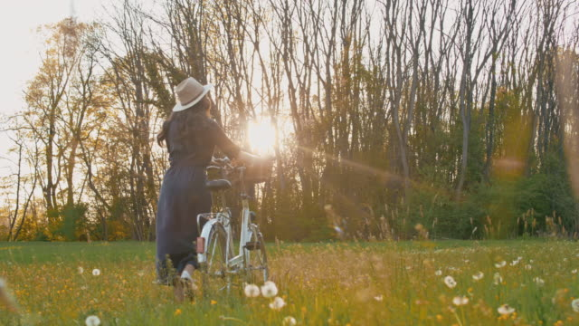 slo mo ws young woman pushing her bicycle through meadow - long hair stock videos & royalty-free footage