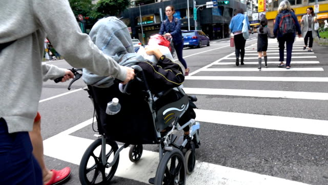 Young woman pushing senior woman on wheelchair crossing the street
