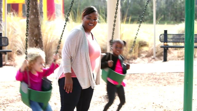 young woman pushing two little girls on swings - preschool child stock videos & royalty-free footage