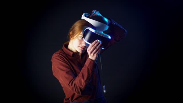 vidéos et rushes de jeune femme met sur un casque de réalité virtuelle avant le match - réalité virtuelle
