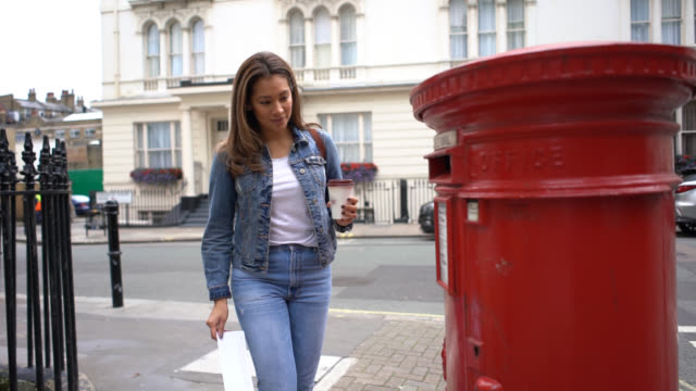 young woman putting a letter in the mail while enjoying a take out coffee - post office stock videos & royalty-free footage