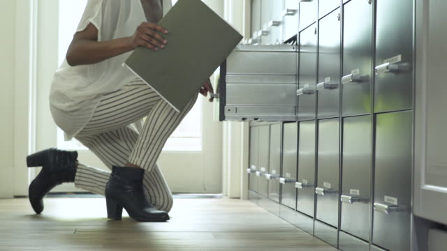 young woman putting away documents - kneeling stock videos and b-roll footage