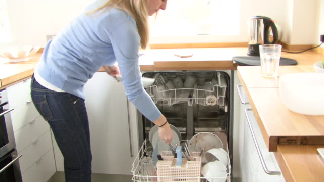 young woman putting dishes in dishwasher; uk - chores stock videos & royalty-free footage