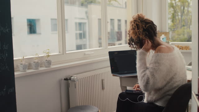 vidéos et rushes de young woman putting in headphones, talking on smartphone at home in berlin - casque audio