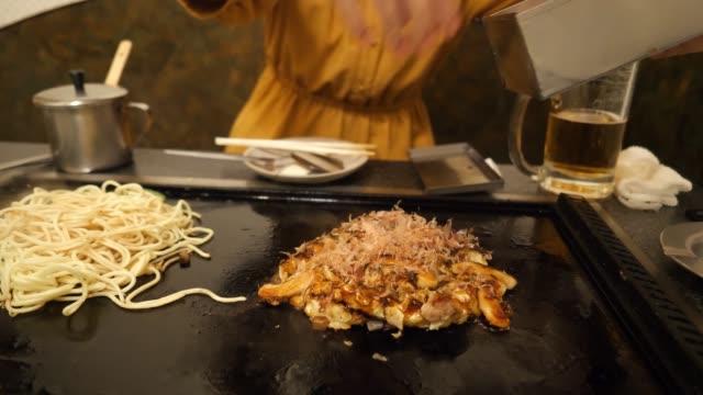 young woman putting 'katsuobushi' on okonomiyaki in japanese restaurant - japanese food stock videos & royalty-free footage