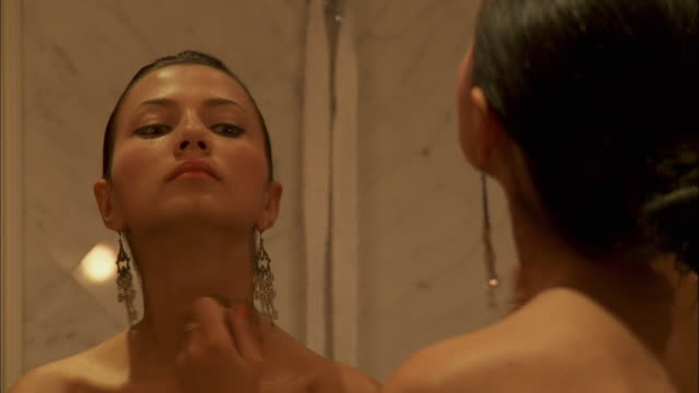 ms young woman putting make up on in front of mirror, rome, italy - ohrring stock-videos und b-roll-filmmaterial