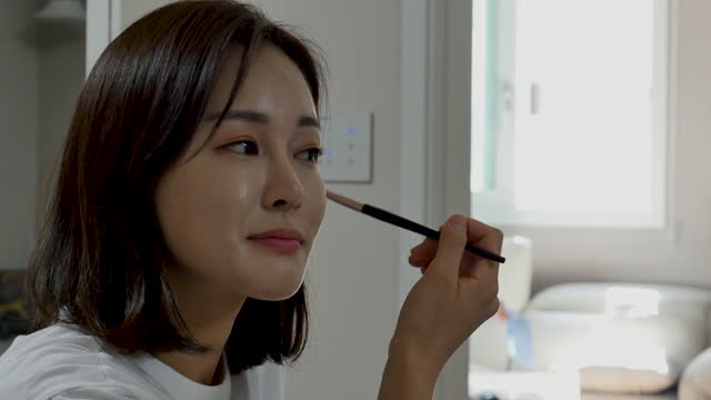young woman putting make-up on her face at home - フェイスブラシ点の映像素材/bロール