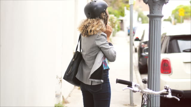 young woman putting on bicycle helmet - cycling helmet stock videos & royalty-free footage