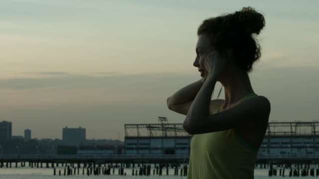 A young woman putting on ear buds before she runs in New York City in slow motion